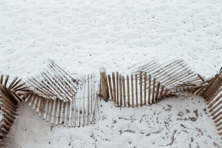 Damaged Wooden Fence On Sand At Beach