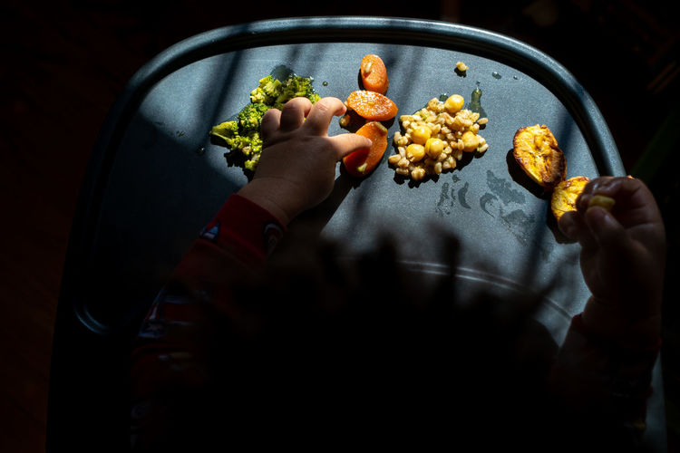 High angle view of a toddler's hands exploring a tray of brightly colored foods during mealtime