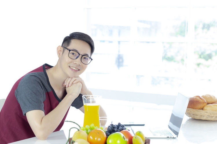 Portrait of smiling man with fruits on table