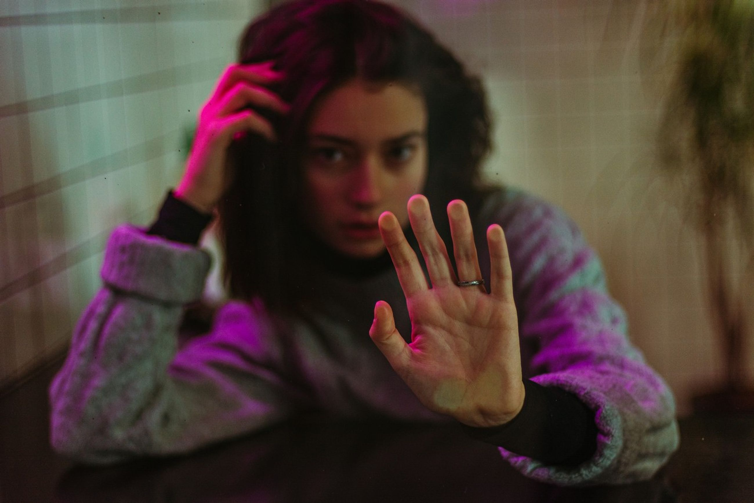 one person, real people, hand, indoors, lifestyles, women, human hand, portrait, adult, front view, young adult, young women, emotion, casual clothing, leisure activity, home interior, focus on foreground, headshot, hairstyle, stop gesture