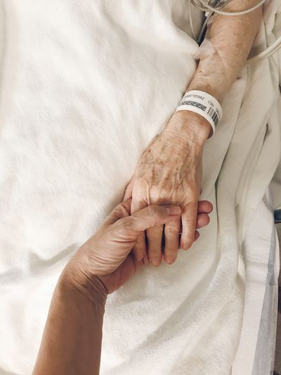 Tenderness Compassion Mother And Daughter Mother Elderly Bed Hands Love Caregiver Medical Healthcare And Medicine Bracelet Gurney Operation Hospital Holding Hands Human Hand Human Body Part Women Adult Body Part Real People High Angle View Personal Perspective Close-up