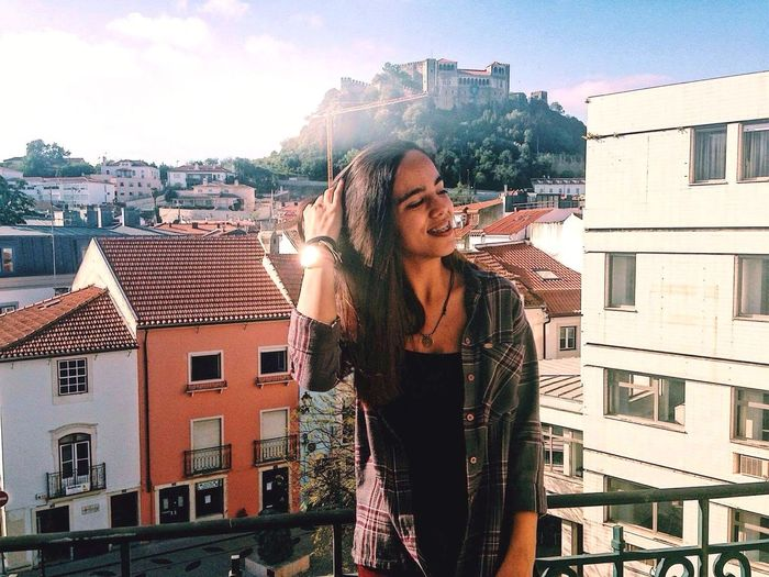 Smiling young woman with hand in hair standing against buildings in city