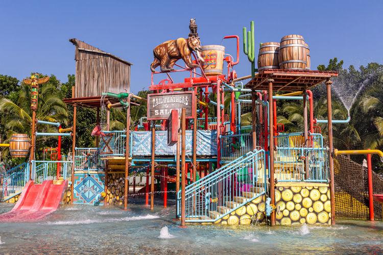 View of amusement park against clear blue sky