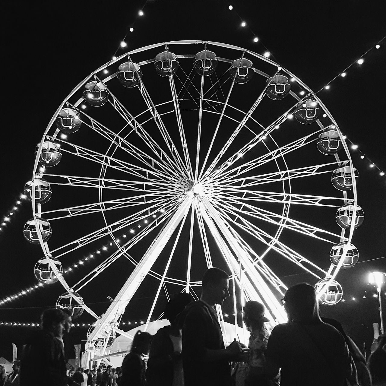 arts culture and entertainment, night, illuminated, leisure activity, amusement park, ferris wheel, large group of people, real people, enjoyment, outdoors, amusement park ride, men, low angle view, women, lifestyles, sky, crowd, people