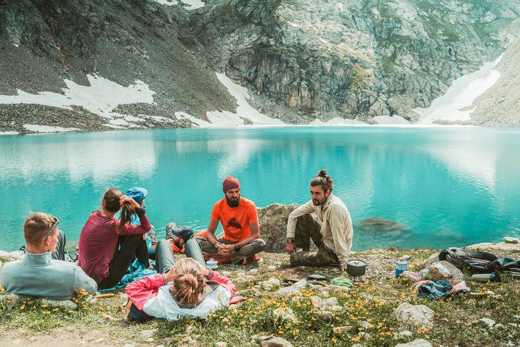 People sitting on rocks by lake