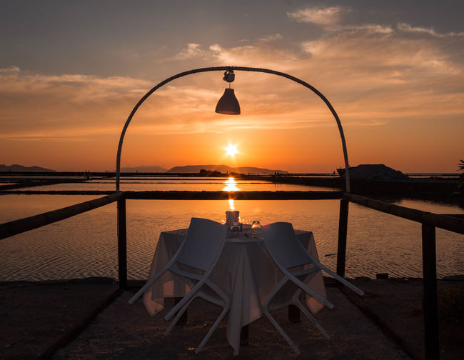 Empty table and chairs by sea against sky during sunset
