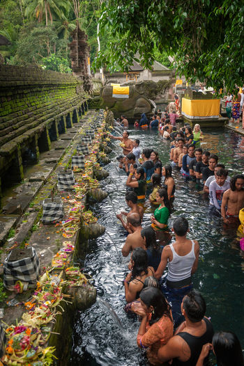 Pura Tirta Empul, Bali, Indonesia. Pura Tirta Empul is a Hindu Balinese water temple located near the town of Tampaksiring, Bali, Indonesia. The temple compound consists of a petirtaan or bathing structure, famous for its holy spring water, where Balinese Hindus go to for ritual purification. The temple pond has a spring which gives out fresh water regularly, which Balinese Hindus consider to be holy or amritha. Tirta Empul means Holy Spring in Balinese. This day is special because of the Full Moon ceremony. ASIA Asian  Bali Balinese Crowd Cultures Day Hindu Hinduism Holy Horizon Over Water Large Group Of People Men Outdoors People Pura Tirta Empul Temple Religion Religious  Southeast Asia Tampaksiring Ubud Water Women Worship Worshipping