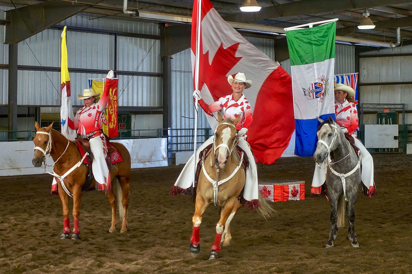 The Canadian Cowgirls perform in Cochrane in Canada. Alberta Canadian Cowgirls Horses Woman Canada Cochrane Flag Indoors
