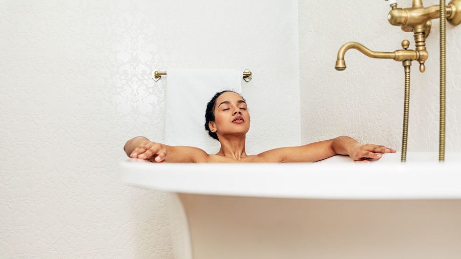 Washing Beautiful Woman Leisure Activity Relaxation Hygiene Lifestyles Indoors  Home One Person Bathroom Bathtub Taking A Bath Real People African American Eyes Closed  Body Care Skin Young Females