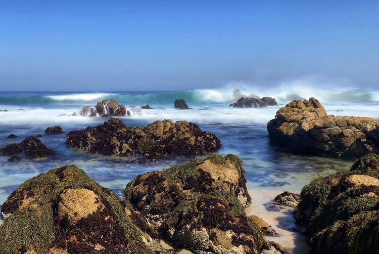 Beautiful scenic landscape of waves crashing on rocky beach along pacific grove coastline, blue sky