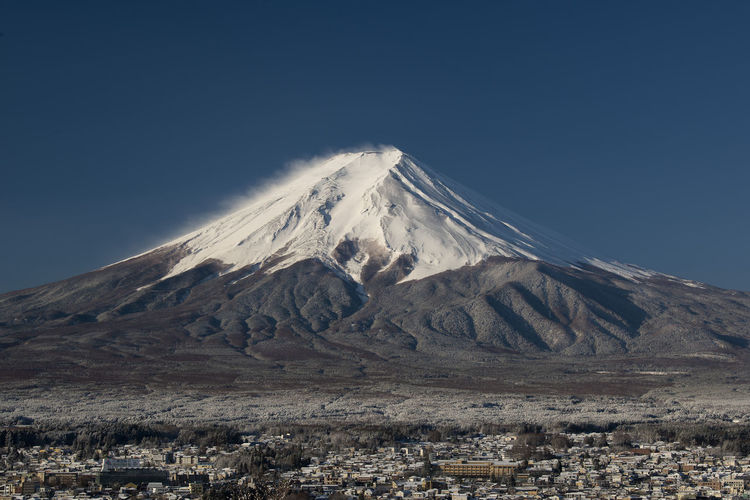 Mount Fuji on close-up with a town below, Japan Yamanashi Winter White Water Volcano View Vacation Travel Town Tourism Sunset Sunrise Summer Spring Snow Sky Season  Scenic Scenery Scene Peak Outdoor No People Nature Natural Mt Fuji MT Mountains Mountain Mount Morning Landscape Landmark Lake Japanese  Japan Ice Holiday Grass Fuji Fresh Evening Dusk Destinations Dawn Blue Beauty Beautiful Background ASIA