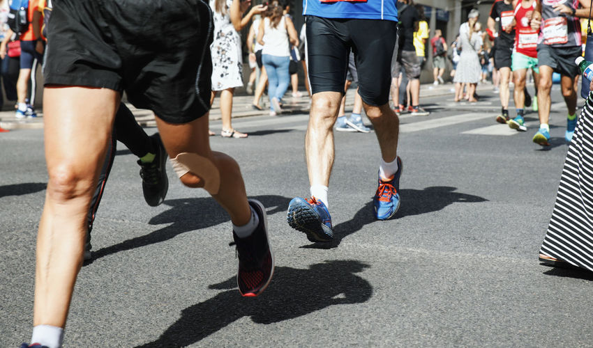 Low section of athletes running on road in city