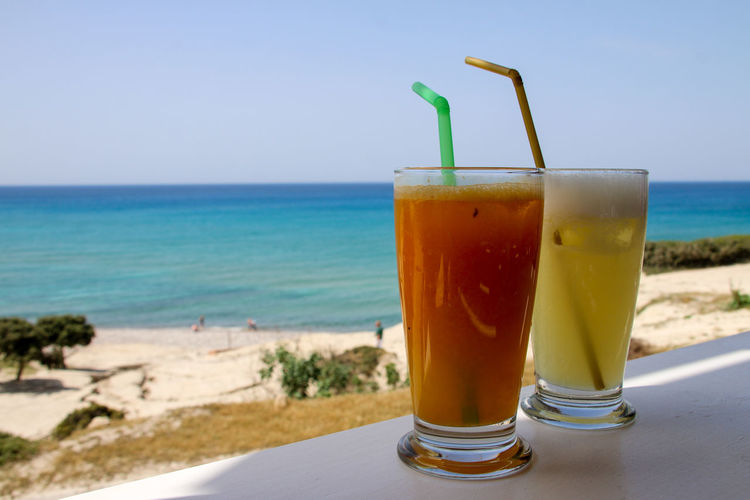 Drink on table at beach against sky