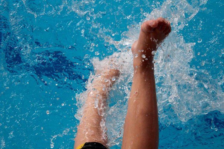 Low section of woman splashing water in swimming pool