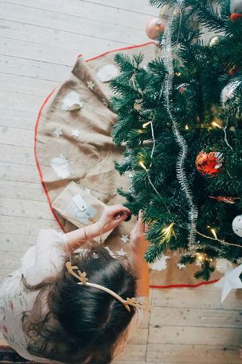 High angle view of woman decorating christmas tree
