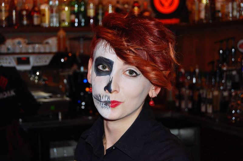 Close-up portrait of woman with face paint at bar
