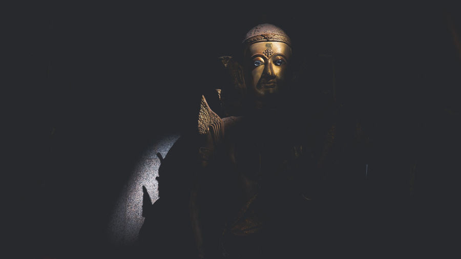 Statue of buddha against black background