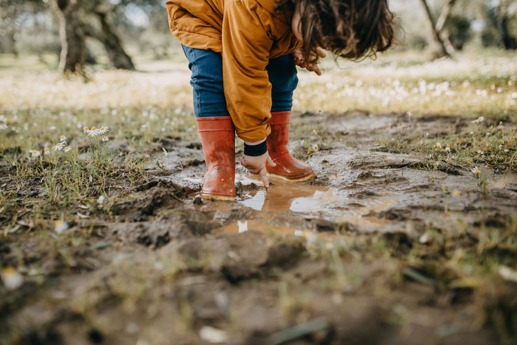 Low section of child standing in mud