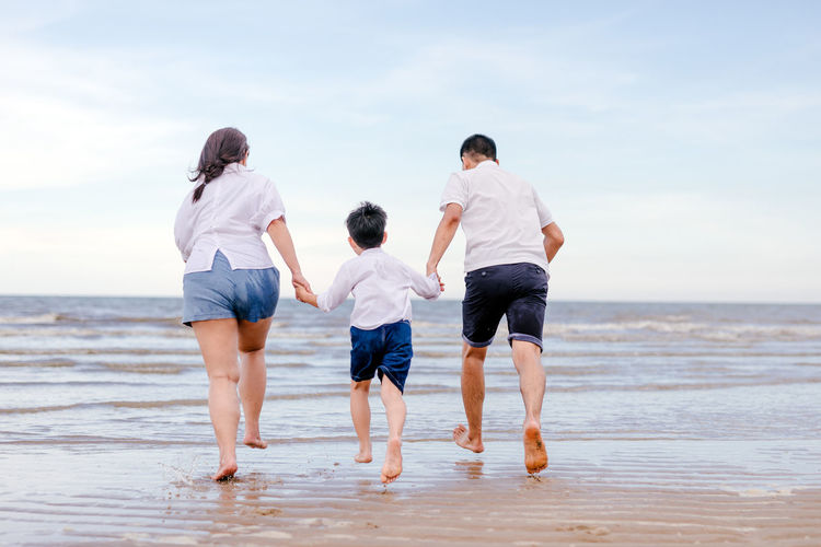 portrait happy family mom dad and son playing together Asian  Beautiful Brother Camera Dad Family Happiness Happy Holiday Love Mother Piggyback Beach Boy Child Family Time Father Lifestyles Mom Parent Playing Portrait Ride Sea Sky