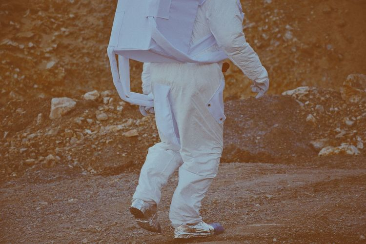 Low section of person wearing space suit walking on land