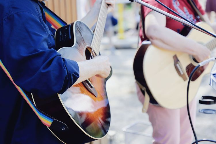 Midsection Of Street Performers Playing Guitar Outdoors