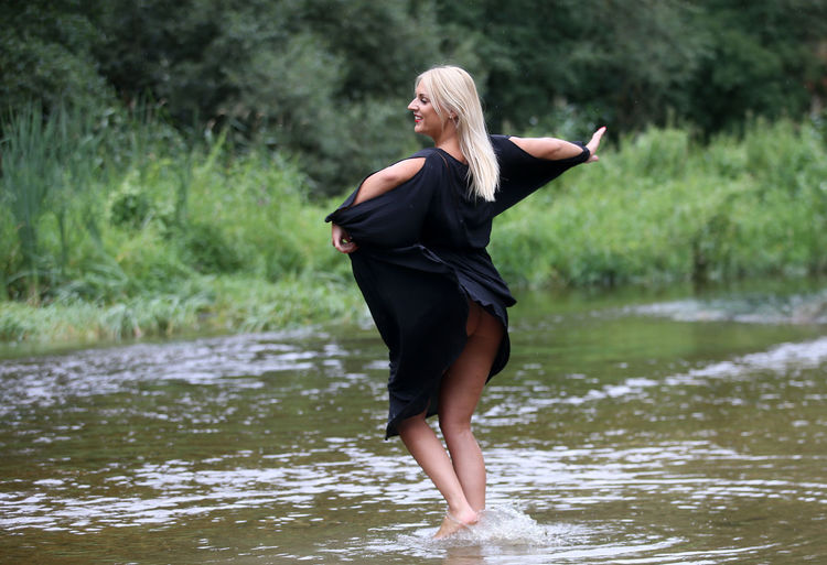 Seductive young woman wearing black dress standing in river