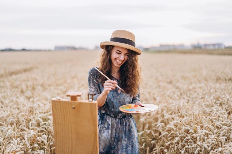 Full length of woman wearing hat on field