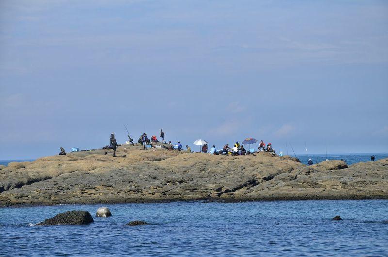 People gathered on huge rock amidst sea