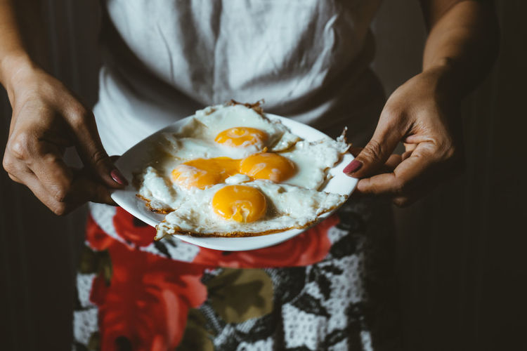 Midsection Of Woman Holding Sunny Side Up On Plate