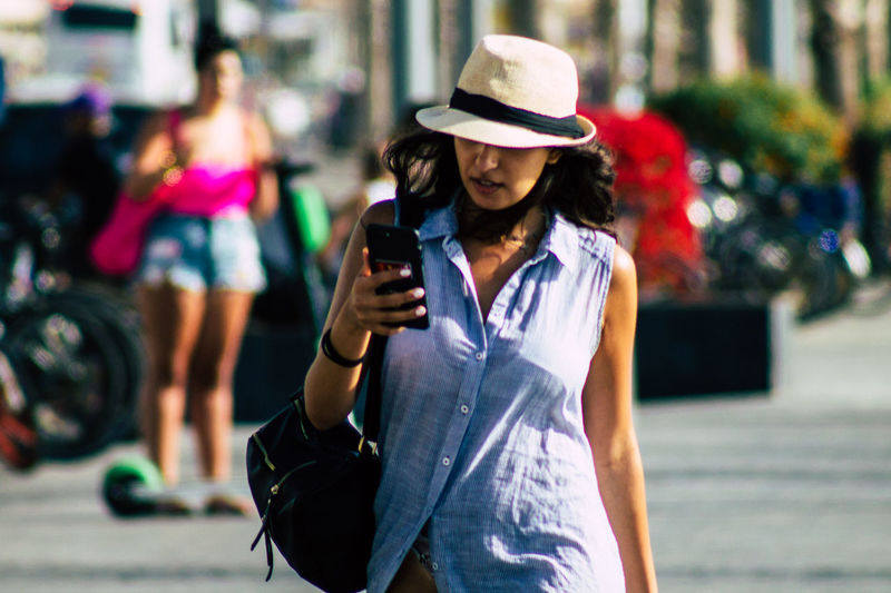 Midsection of woman holding mobile phone in city