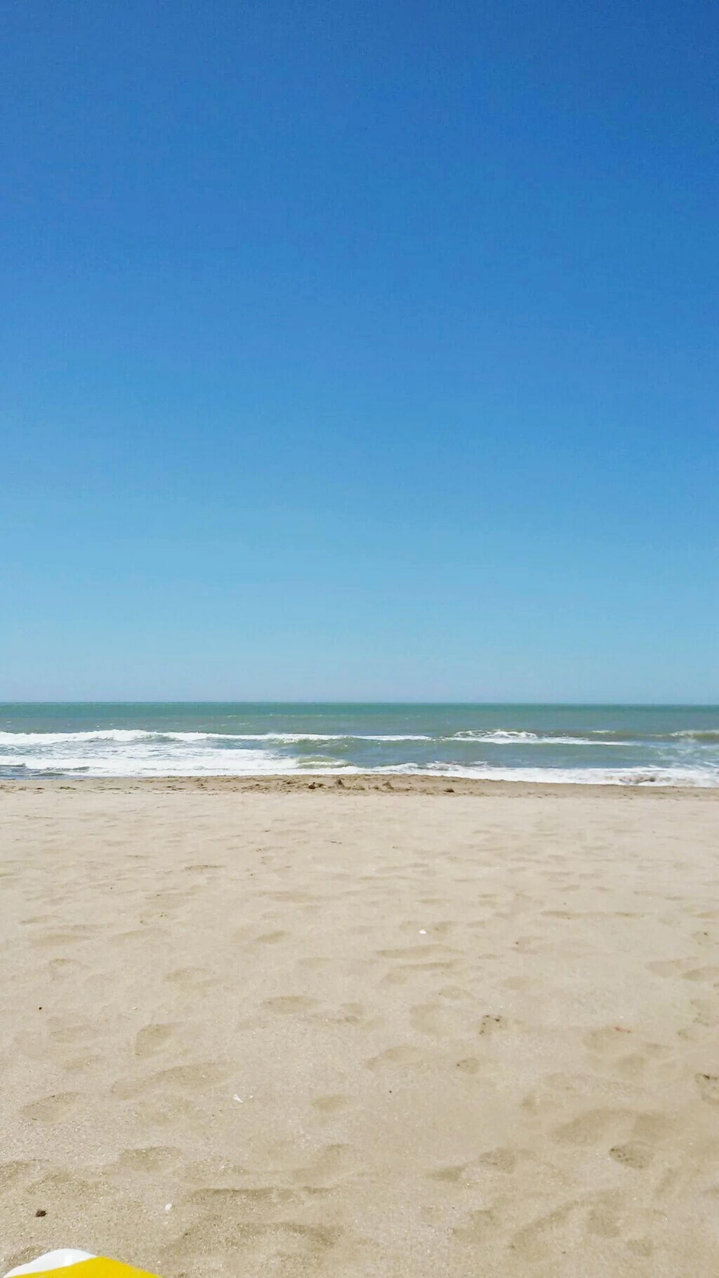 clear sky, sea, copy space, horizon over water, beach, sand, water, shore, blue, tranquil scene, tranquility, scenics, beauty in nature, nature, idyllic, outdoors, day, calm, remote, wave