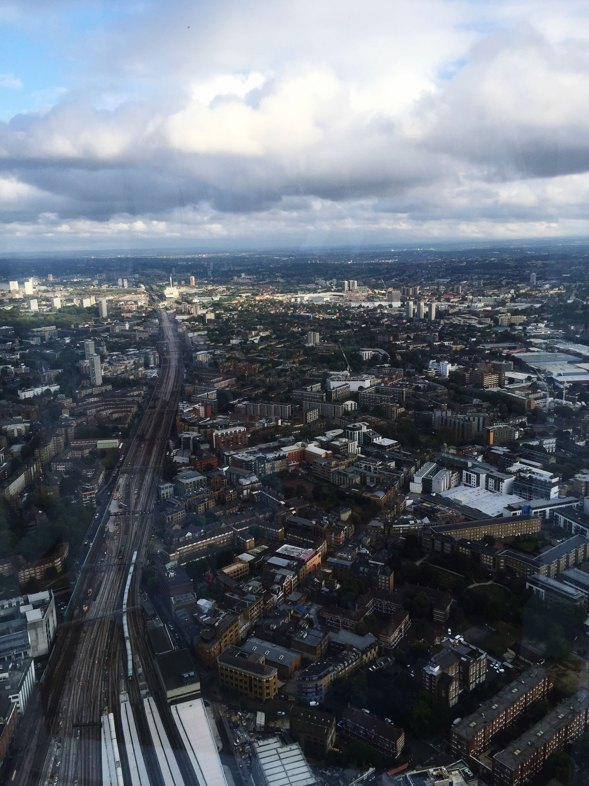cityscape, city, architecture, built structure, building exterior, crowded, aerial view, wide shot, sky, wide, travel destinations, city life, cloud - sky, residential district, cloud, outdoors, day, cloudy, tourism, horizon over land, urban road, horizon, development, urban scene, office building