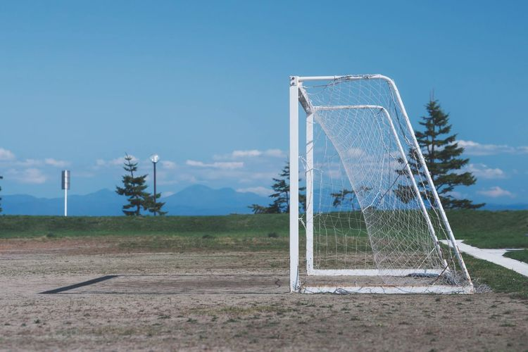 Goal post on soccer field against blue sky