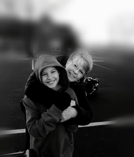 Portrait of smiling grandmother embracing granddaughter at playground