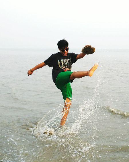 Full length of man jumping on beach against sky