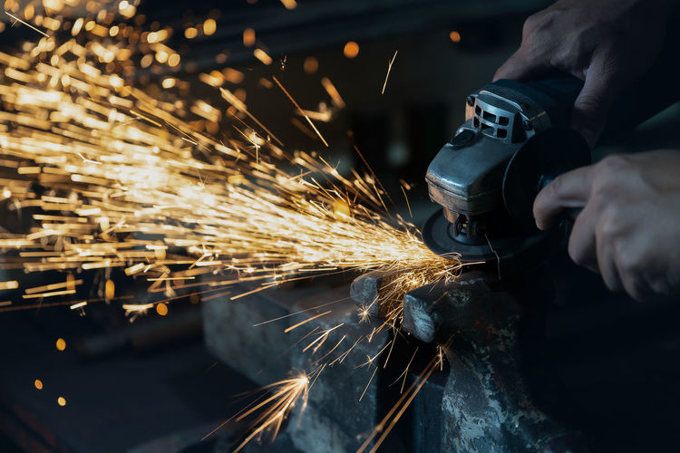 Human hands are grinding in factory Human Hand Industry Sparks Hand Working Holding Metal Factory Grinder Work Tool Skill  Finger Manufacturing Equipment Welding Iron - Metal Body Part Equipment