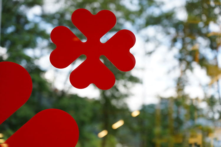 Low angle view of red heart shape against trees
