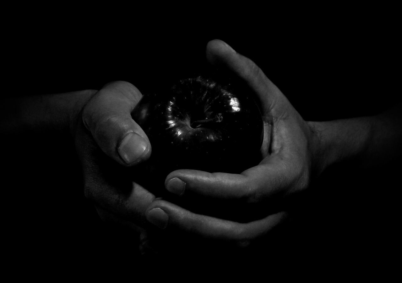 CLOSE-UP OF MAN HOLDING APPLE OVER BLACK BACKGROUND