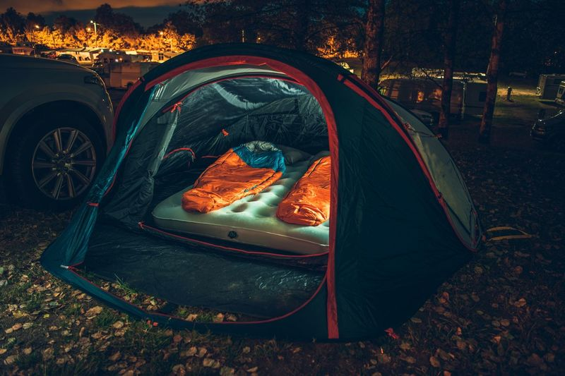 Inside Illuminated Tent on the Campsite at Night. Two Sleeping Bags Inside. Traveling with Tent Theme. Campsite Nature Traveling Camping Car Day Destination Food Forest Land Leaf Mode Of Transportation Motor Vehicle Nature No People Orange Color Outdoors Plant Part Sleeping Bag Tent Transportation Tree
