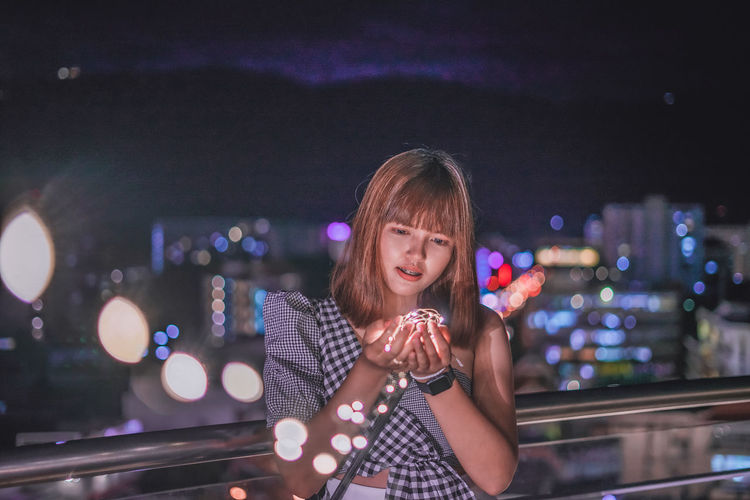 Woman holding illuminated string light against cityscape at night