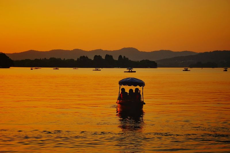 Sunset Reflection Silhouette Water Outdoors Mountain Landscape Scenics Tranquility Lake Travel Destinations Nature Beauty In Nature Vacations China View FUJIFILM X-T10 Light And Shadow Lake View Travel West Lake, Hangzhou Hangzhou,China Warm Glow Yellow Tranquility Floating On Water