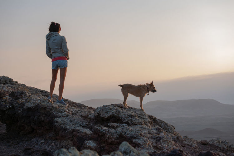 girl on the top of the volcano with her dog Canine Dog Domestic Domestic Animals Full Length Leisure Activity Lifestyles Mammal One Animal People Pets Real People Rear View Rock Rock - Object Sky Solid Standing Sunset