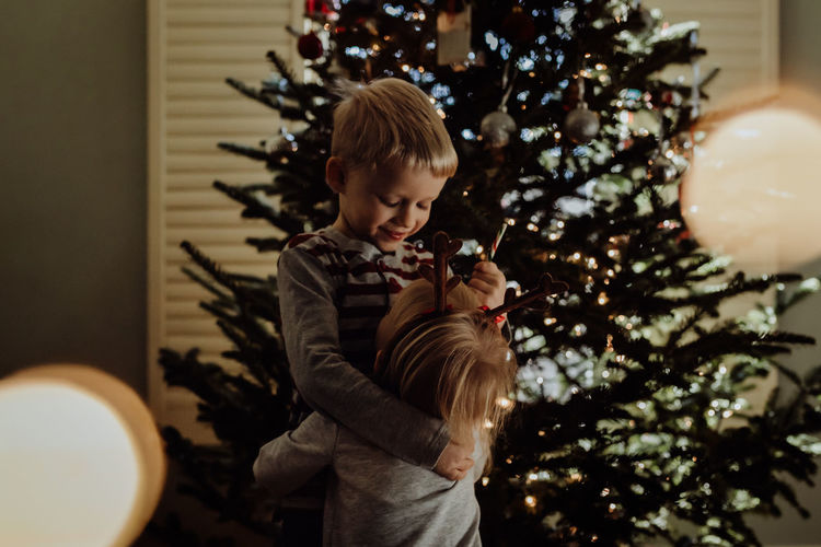 Christmas Hug Love Siblings Blond Hair Bonding Childhood Christmas Christmas Decoration Christmas Tree Cute Happiness Home Interior Indoors  Lifestyles Real People Smiling Tree