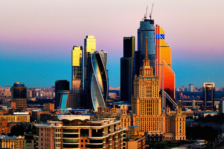 Skyscrapers in city at sunset