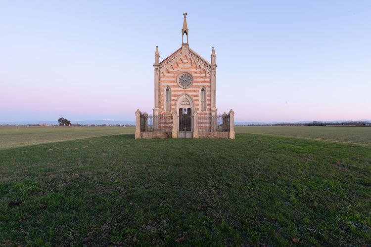 Church on field against clear sky