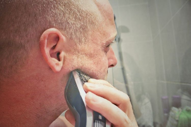 Close-up of man shaving beard with electric razor