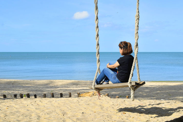 Woman sitting on swing at beach against sky