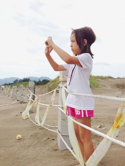 Side View Of Girl Photographing While Standing By Fence At Beach