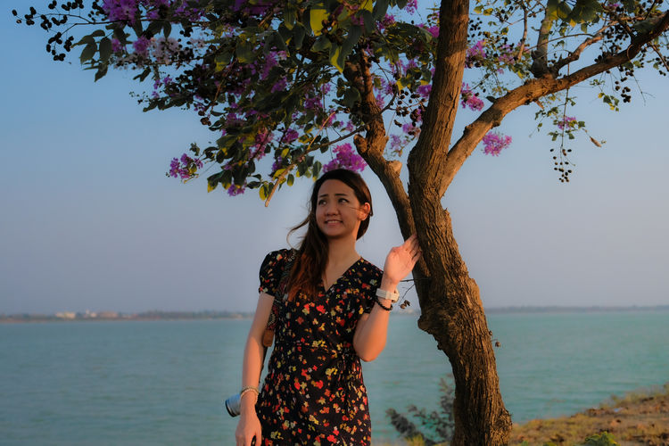 Smiling woman looking away while standing by tree trunk against sea and sky