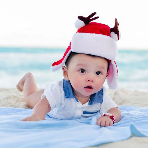 Portrait of cute baby girl lying on bed at beach